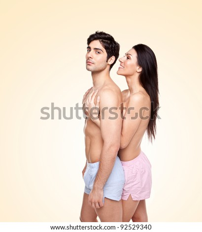 Romantic Couple Enjoying Foreplay with a smiling topless young woman caressing the mans chest from behind, studio portrait - stock photo
