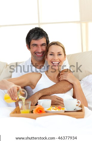 Romantic couple having breakfast lying in the bed at home - stock photo