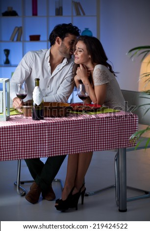 Romantic couple having dinner at home. Man whispering to woman. - stock photo