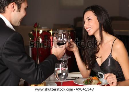 Romantic couple having dinner, clinking glasses - stock photo