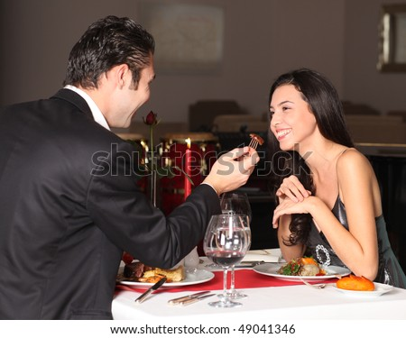 Romantic couple having dinner, man feeding woman - stock photo