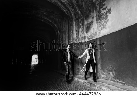 Romantic couple holding hands in dark old street hallway b&w