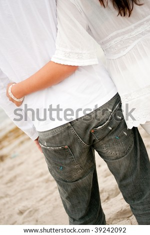Romantic couple hugging by the beach - stock photo