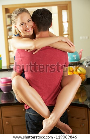 Romantic Couple Hugging In Kitchen - stock photo