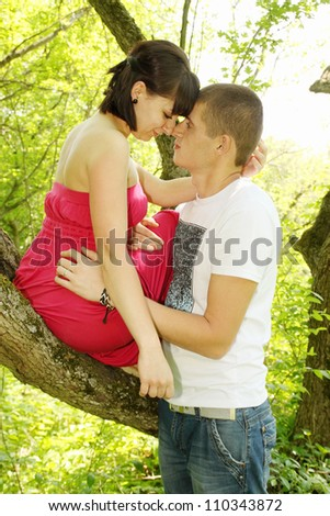 Romantic couple hugging in the woods under a tree