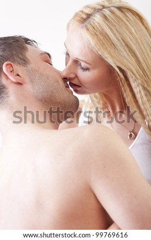 Romantic couple in bed kissing - stock photo
