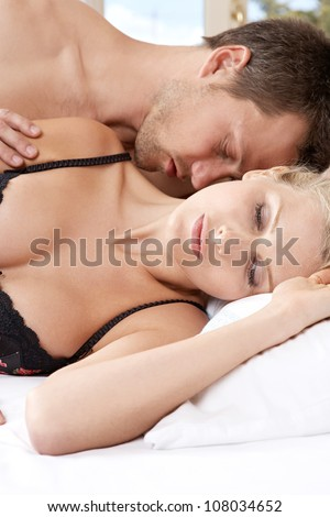 Romantic couple in bed, with man kissing woman's neck. - stock photo