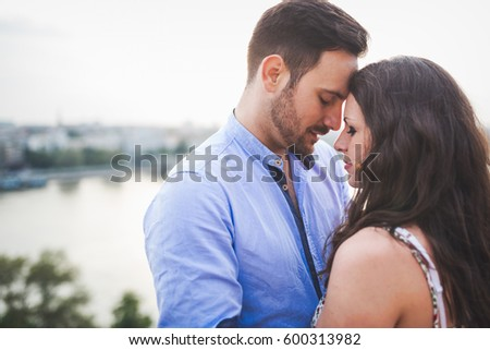 Romantic couple in love cuddling and kissing outdoors during sunset