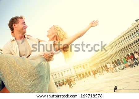 Romantic couple in love having fun embracing and laughing in Venice, Italy on Piazza, San Marco. Happy young couple on travel vacation on St Mark's Square. Man carrying woman in arms in sunset. - stock photo