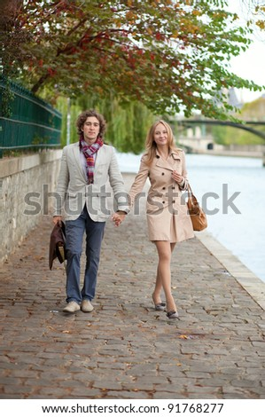 Romantic couple in Paris, walking by the embankment