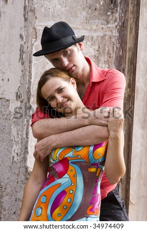 Romantic couple is embracing. Portrait of a happy couple near bare walls.  Charming young girl and boy spending quality time.  Fashion man model wear red shirt and hat near bare walls. - stock photo