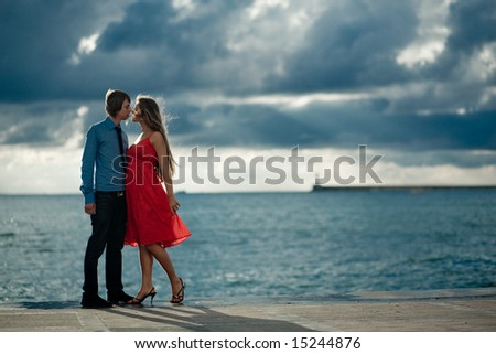Romantic couple kissing at stormy sunset - stock photo