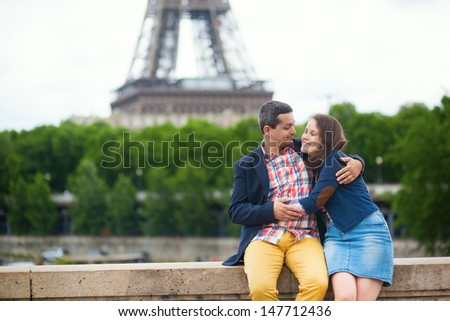 Romantic couple kissing near the Eiffel tower - stock photo