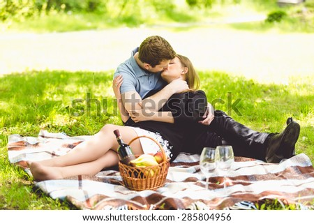 Romantic couple kissing on blanket at park at sunny day - stock photo