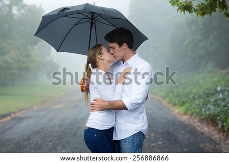 romantic couple kissing under an umbrella - stock photo