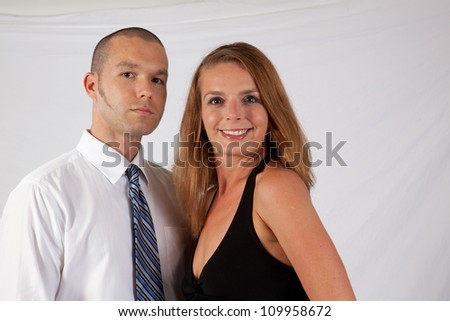 Romantic couple, man and woman, standing in an embrace and looking at the camera with a smile - stock photo