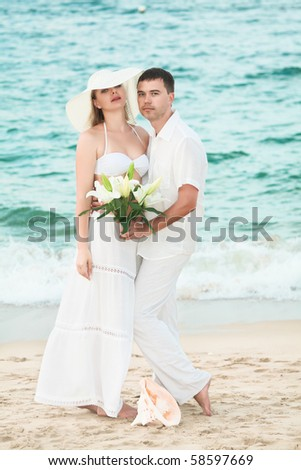 Romantic couple near the ocean with flowers