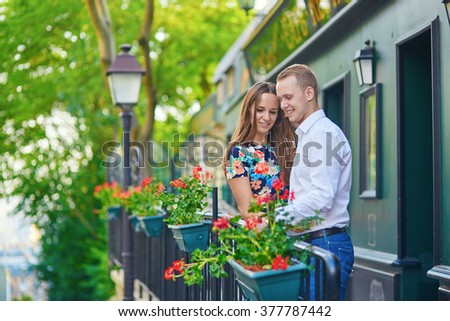 Romantic couple on the balcony decorated with flowers on Montmartre, Paris