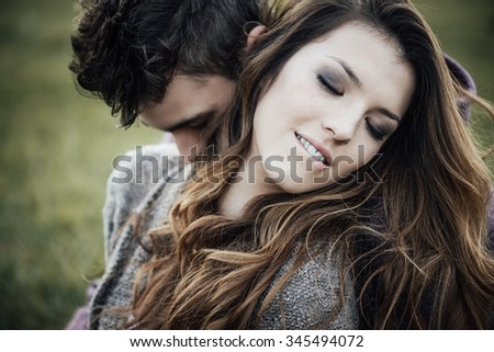 Romantic couple outdoors, they are sitting on grass and hugging, she is biting her lip - stock photo