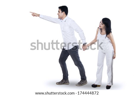 Romantic couple pointing at empty copy space on white background