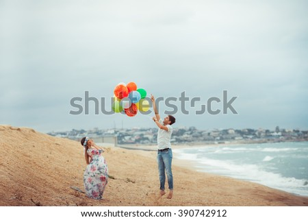Romantic couple relaxing on the beach and enjoying beautiful sea view, side view, spending time together, summer vacation concept