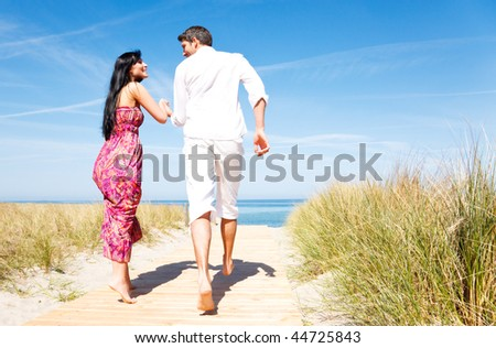 Romantic couple running to holiday vacation in summertime with blue sky beyond holding eachother - stock photo