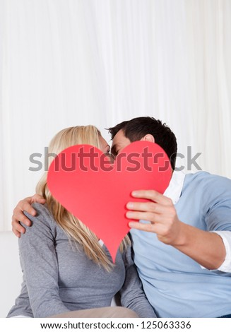 Romantic couple sitting on a sofa in a loving embrace laughing as they hold up a red paper heart for Valentines day - stock photo