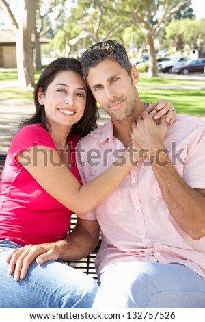 Romantic Couple Sitting On Park Bench Together