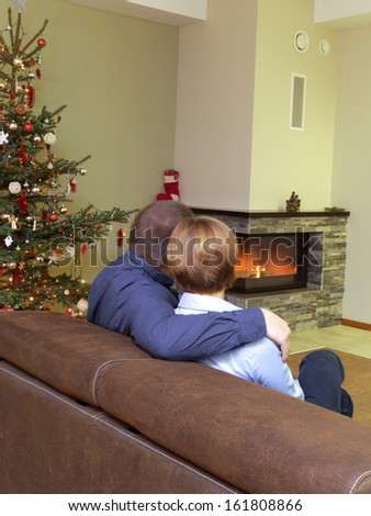 Romantic couple sitting on sofa near christmas tree looking at the lit fireplace - stock photo