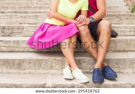 Romantic couple sitting together on stairs outdoors - stock photo
