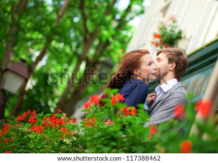 Romantic couple together on balcony of their house or hotel with blossoming geranium - stock photo