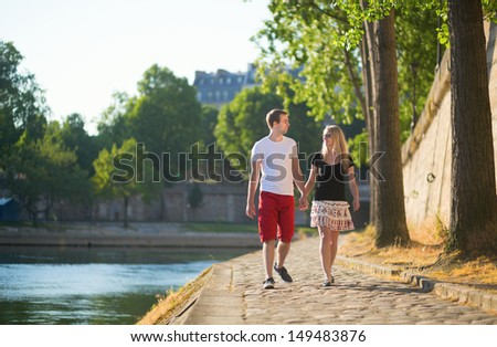 Romantic couple walking near the Seine - stock photo