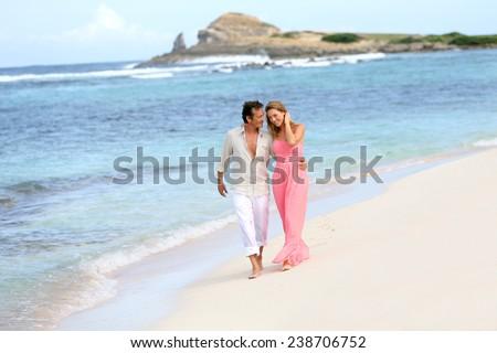 Romantic couple walking on a sandy beach - stock photo