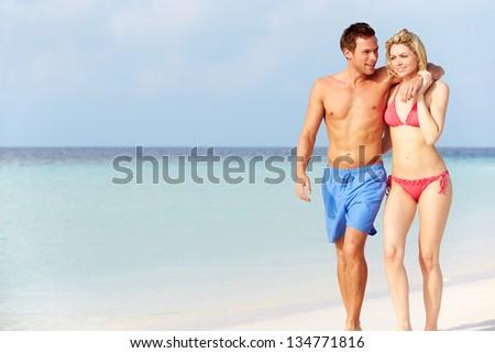 Romantic Couple Walking On Beautiful Tropical Beach - stock photo