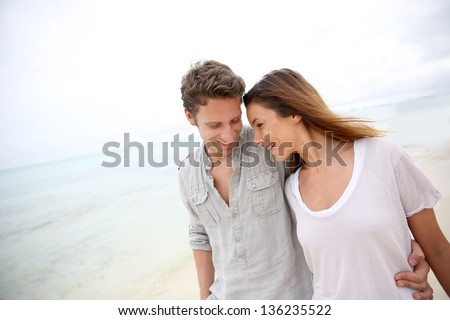 Romantic couple walking on the beach - stock photo