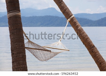 Romantic cozy hammock of the palm on the tropical beach by the sea - stock photo