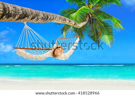 Romantic cozy hammock with straw hat under coconut palm tree at tropical paradise ocean beach in bright sunny summer day - vacation background - stock photo