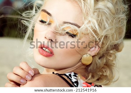 Romantic cute portrait of beautiful cheerful blonde model with orange shadows - stock photo