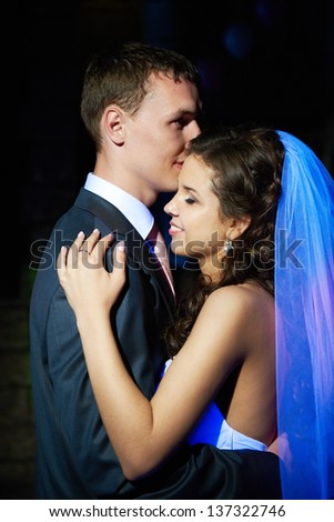 Romantic dance young bride and groom in dark banqueting hall