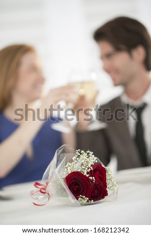 romantic dating at restaurant focus on flower bouquet - stock photo