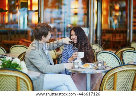 Romantic dating couple drinking coffee and eating traditional French croissants in cafe in Paris