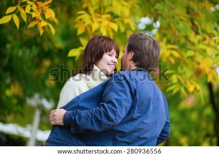Romantic dating couple in park on a bright fall day, having fun, autumn leaves in the background - stock photo