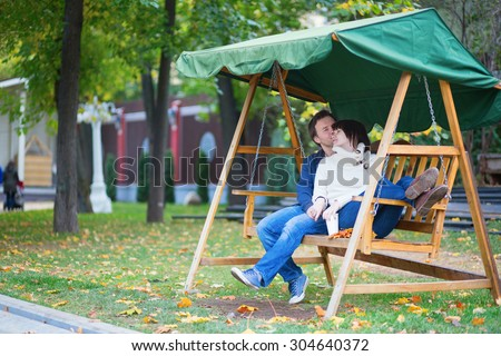 Romantic dating couple on the swing on a bright fall day, man offering his girlfriend bunch of autumn leaves