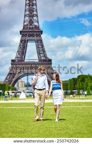 Romantic dating couple walking in Paris near the Eiffel tower - stock photo