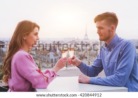 romantic dinner for couple in luxurious restaurant in Paris with panoramic city view and Eiffel tower - stock photo