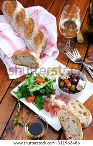 Romantic dinner for two; italian antipasto platter with parma ham, rocket, olives, baguette and wine  - stock photo