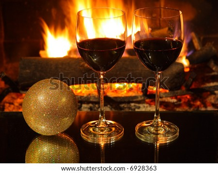 Romantic dinner for two, two glasses of red wine, fireplace, Christmas decoration. - stock photo