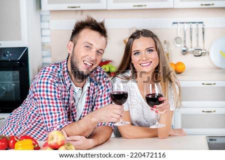 Romantic dinner in the kitchen. Beautiful loving couple holding glasses of wine in the kitchen while they cooking dinner. Young people raise their glasses and look at the camera - stock photo
