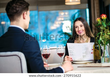 Romantic dinner in the restaurant. Young couple sitting at a table at each other and smiling lovingly at the restaurant until a woman holding hands in the menu - stock photo