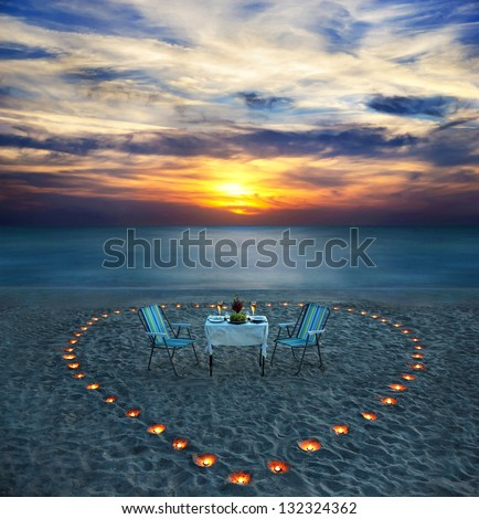 romantic dinner on sea beach with candle heart on the sand - stock photo